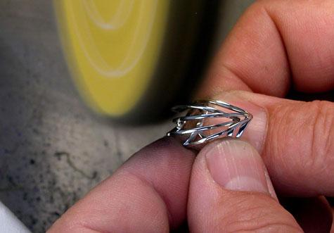 Jeweler polishing a platinum ring at a polishing machine.