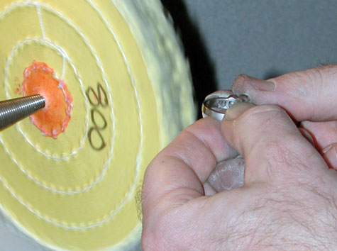 "A jeweler preparing to polish a platinum ring using the yellow-treated wheel labeled ""800"""