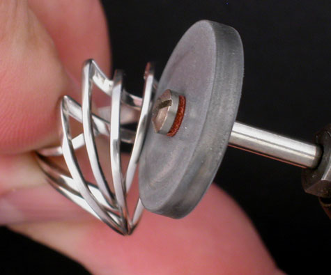 Close-up view of a jeweler using an abrasive wheel to prefinish a platinum ring that incorporates flat wires as part of the design
