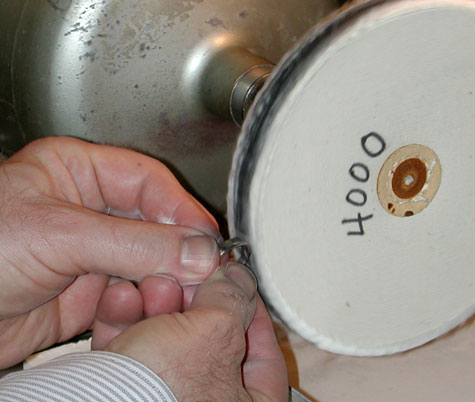 Jeweler finishing the four-prong, platinum solitaire on the 4000 grit abrasive wheel