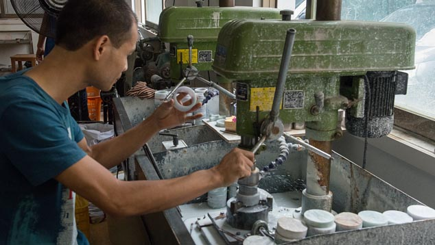 Pingzhou artisan using circular saw bit to cut jadeite disks