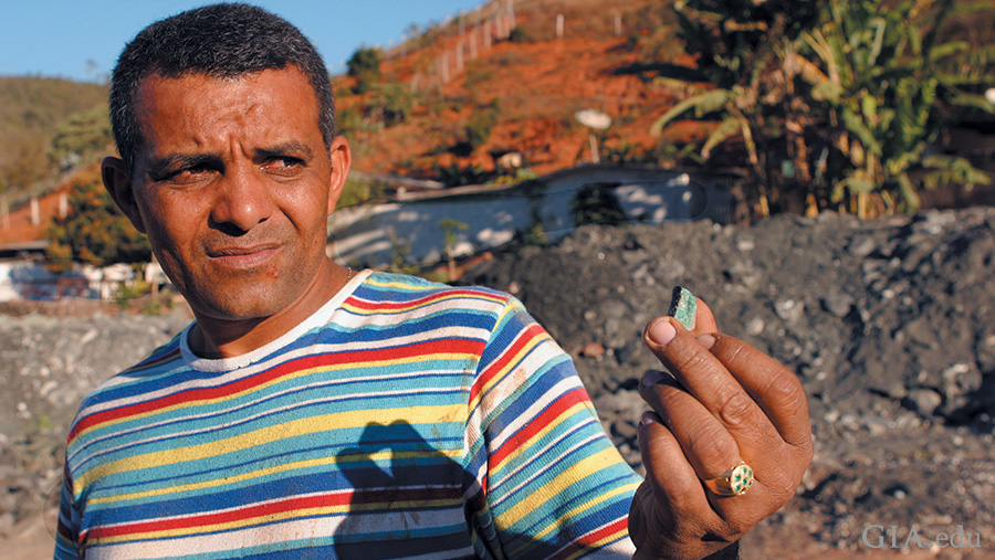 An independent miner at the Capoeirana mining area holds a rough emerald. Photo: Eric Welch/GIA