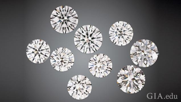 A group of nine round brilliant cut man-made diamonds on a black background.