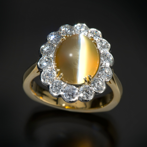 """This chrysoberyl ring features a very fine cat's-eye, which visually divides the cabochon in half and reflects a light and dark color called """"milk and honey."""" These attributes make the cat's-eye chrysoberyl a collector gemstone. Courtesy Richard Krementz Gemstones. Photo by Robert Weldon/GIA"""