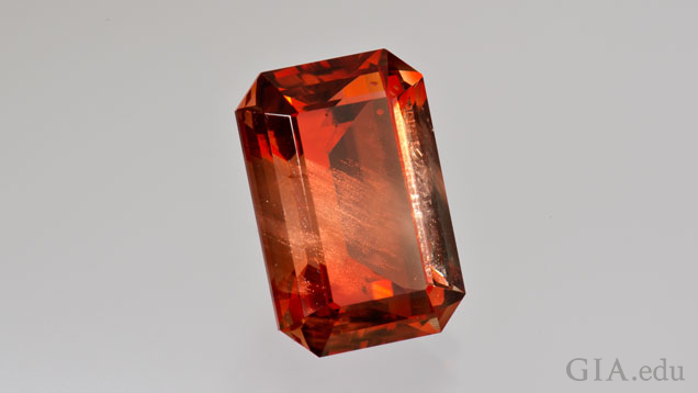 A rectangle, step cut, bright orange sunstone on a light gray background.
