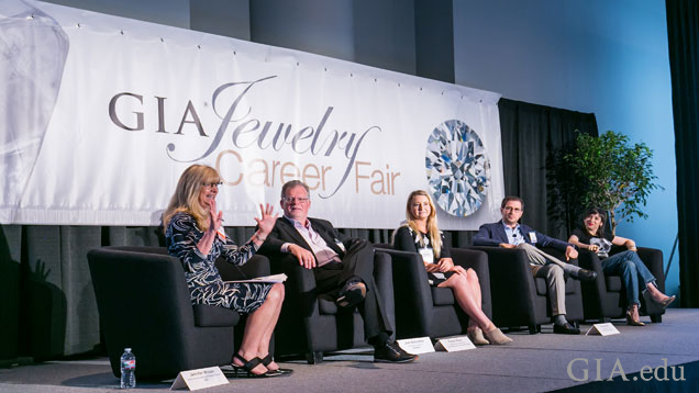 Five people sitting down on stage during a panel discussion at the GIA Jewelry Career Fair in New York City.
