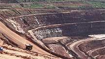 大きな鉱山で同心円状に敷かれた道路を走行するトラック。
