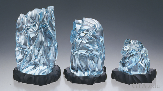 Three light-to-medium blue carved sculptures sit in a line – from larger to smaller.