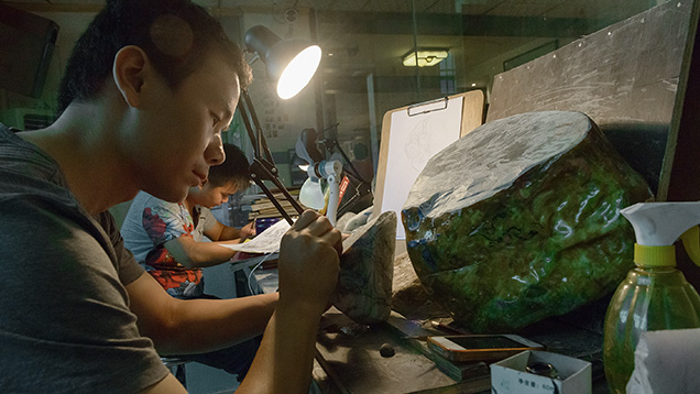 Artist marking up jade for carving