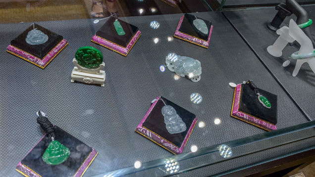 Jadeite pendants, decorations and bangle in display case