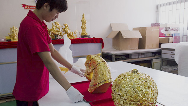 Chinese worker with gold statue