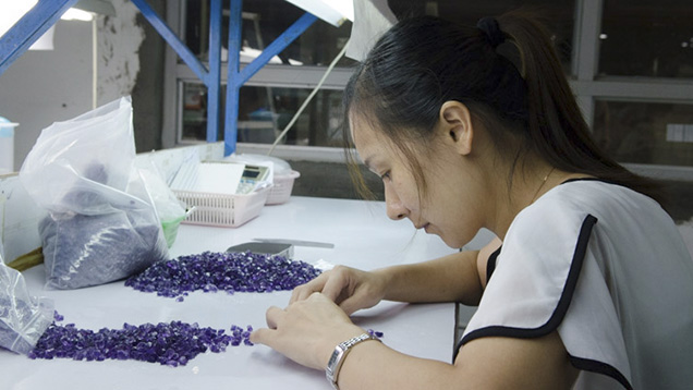 Chinese woman examines rough gemstones
