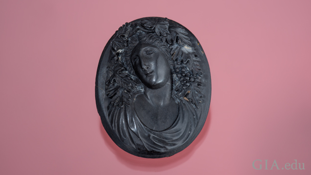 The goddess Bacchante is carved in high relief in black lava and shows fine detail of leaves and clusters of grapes in her hair.