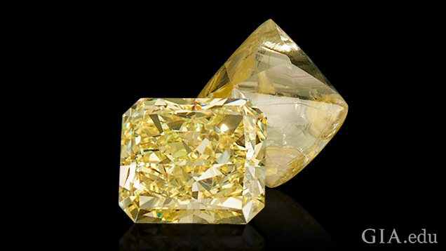 A polished and cut yellow diamond sits in front of a rough yellow diamond.