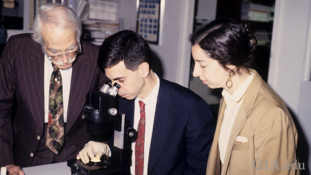 Two men and a woman gather around a microscope.