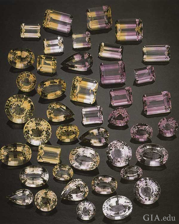 Arrangement of faceted citrine, amethyst, and ametrine gems in varying shades of yellow and purple from the Anahí mine crystals exhibit the November birthstone.