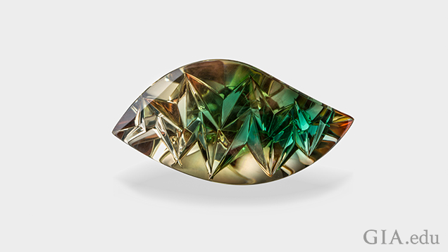 A carved wave-shaped gem with brown on the outer area and green in the center.