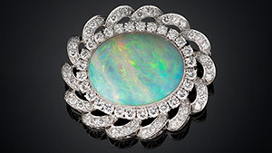 An oval shaped 33.40 ct white Australian opal and diamond pendant/brooch set in platinum.