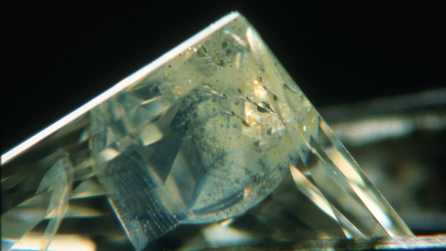 Fracture filling can improve the apparent clarity of a diamond, but they may not always last. In this example, the filling has degenerated due to heating during a jewelry repair. Courtesy of Gary Roskin, G.G., F.G.A.