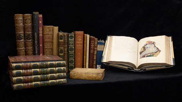 A sampling of beautiful rare books displayed in a row and in several piles – one with its pages open.