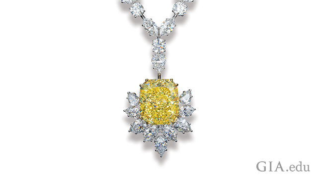 Image of large yellow diamond in setting with other white diamonds.