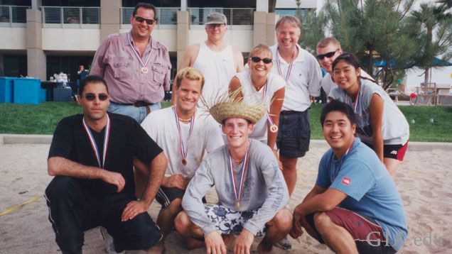 A group of 11 casually dressed students pose for a group photo in the sand of the volleyball court at GIA's Carlsbad campus.