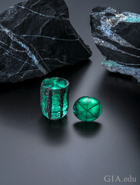 A barrel shaped piece of traphiche emerald rough and a cabochon of it sit in front of two large chucks of shale rock.