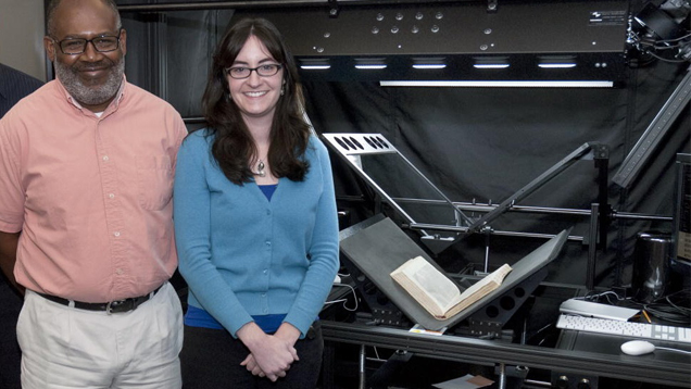 Two research librarians stand in front of the high-tech book scanner.