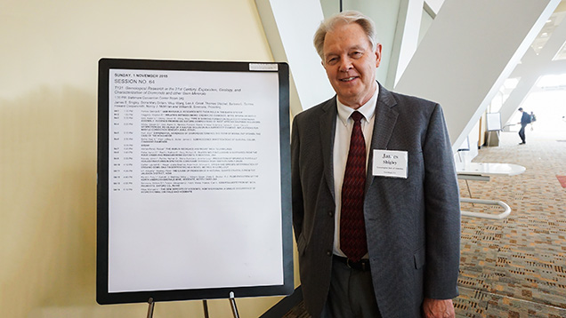 Dr. James Shigley standing next to the schedule of oral presentations