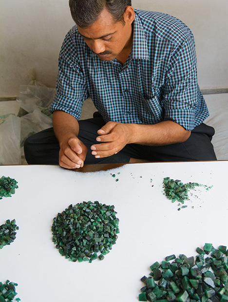 Man sorting rough emerald