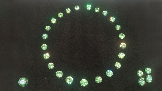 "A suite of 28 unset ""apple green"" Namibian demantoid garnets displayed as a necklace."