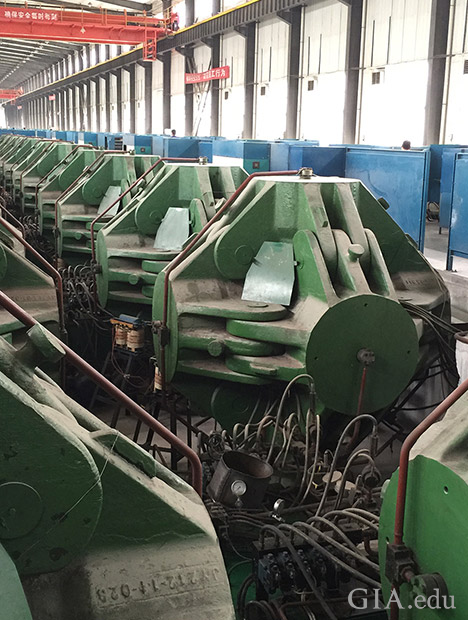 A row of HPHT synthetic diamond presses machinery in a large factory.