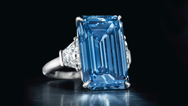 The 14.62 ct. emerald cut Fancy Vivid Blue Oppenheimer diamond is flanked by diamonds in a ring setting.