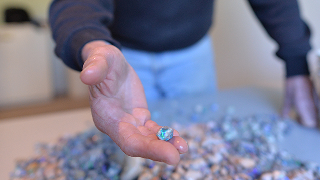 Man showing a piece of rough opal from a pile of stones