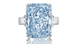 A 24.18 ct. cut-cornered, rectangular, mixed cut Fancy Intense blue diamond flanked with tapered baguette-cut diamonds.