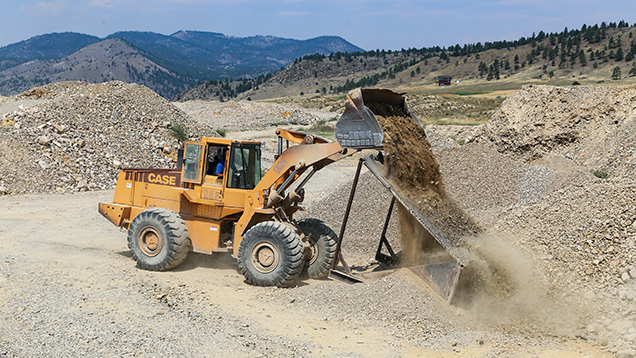 Bulldozer dumping dirt on grizzly