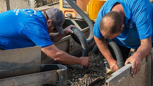 Men vacuuming dirt in the jig