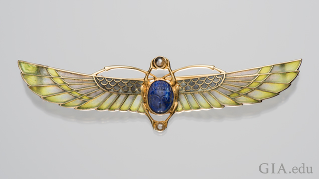 A scarab brooch with two sets of wings – one set is short, the other elongated. The body is a lapis lazuli and the long wings are a blue-green enamel.