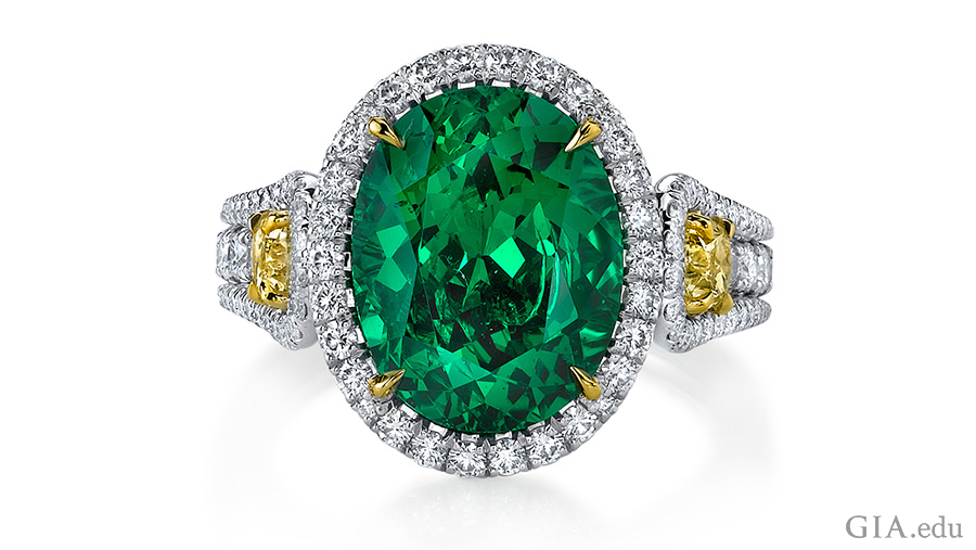 5.55 carat oval cut tsavorite garnet ring set in platinum with two fancy yellow diamonds and 136 round diamonds shows off the January birthstone.