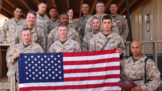 Diaz stands with 13 fellow Marines as they pose in camouflage with the American flag.