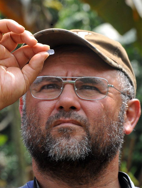 Close up shot of Manuel Diaz as he holds a blue spinel up in front of his eyes.