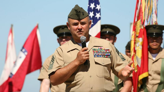 Manuel Diaz, in dress uniform, holds a microphone to address the crowd at his retirement ceremony. The American flag and U.S. Marine Corp flag are behind him, along with other flags and Marines.