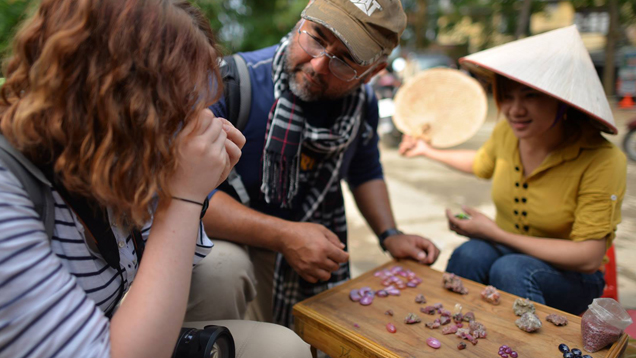 Manuel talks to two women as he looks at gems in a Vietnam gem market. The three sit around a small wooden table with gems separated into piles on it.