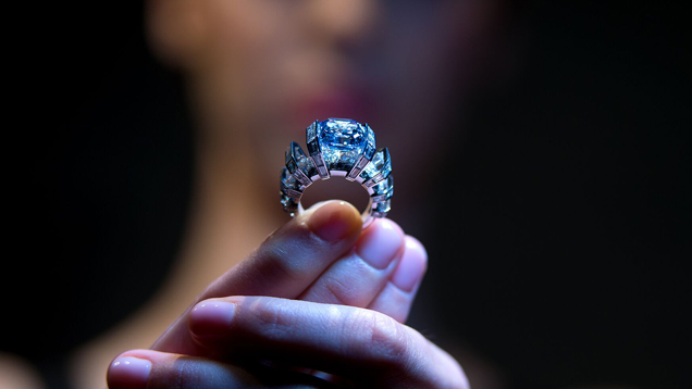 "A woman holds the ""Blue Sky"" diamond ring. Her face is obscured, but there is a close-up of her fingers holding the ring."