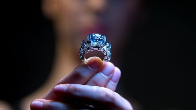 """""""Blue Sky""""(ブルースカイ)ダイヤモンドのリングを手にする女性。 彼女の顔は隠れているが、リングを手にしている彼女の指のクローズアップ写真である。"""