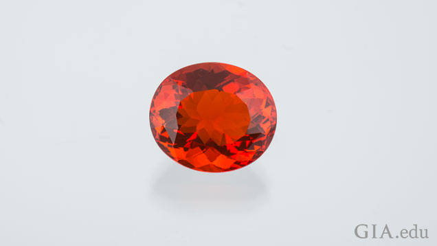 Oval, bright orange fire opal on a gray background.