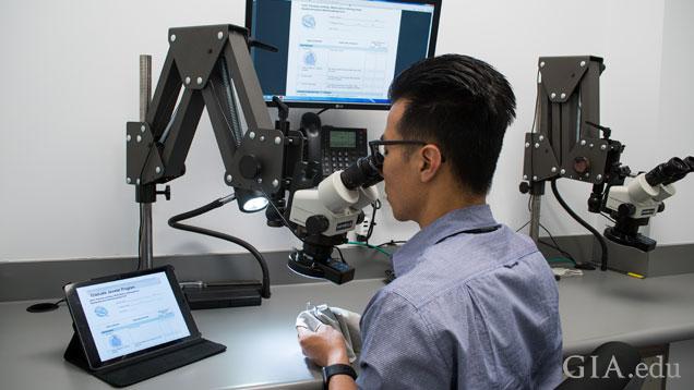 一位男士坐在显微镜前观察一件珠宝。