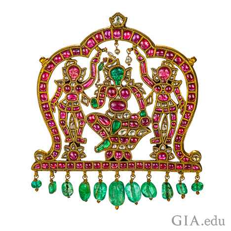 Gold pendant featuring carved drawings of indian gods and emeralds and rubies