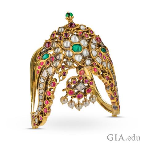 ダイヤモンド、ルビー、エメラルド、真珠を特徴とし、彫刻が施された華やかな金製アームレット。