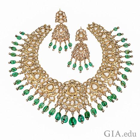 エメラルドとダイヤモンドがゴールドにセットしているネックレスと2つのイヤリングのセットを表示する画像